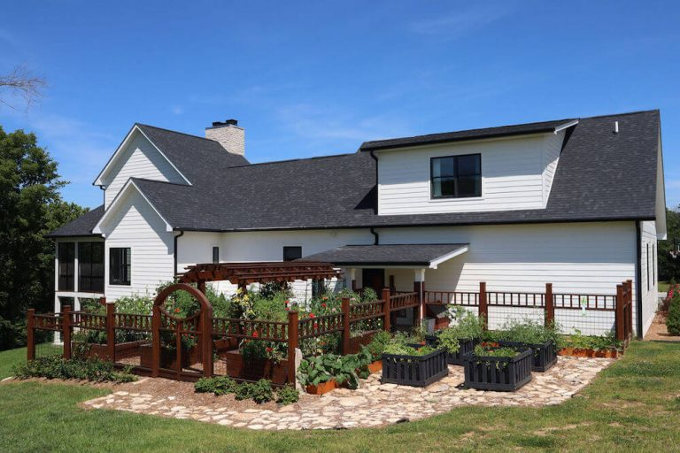 Exterior view of custom build home in Bloomington IN with fenced in garden area