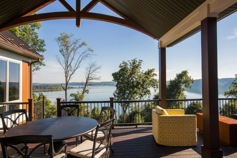 Patio area overlooking the lake and surrounding trees with seating