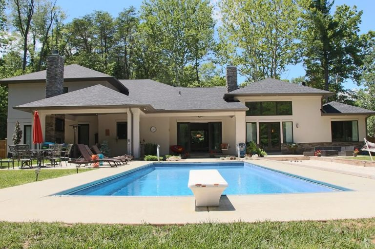 Back view of custom built home in Bloomington with swimming pool and diving board
