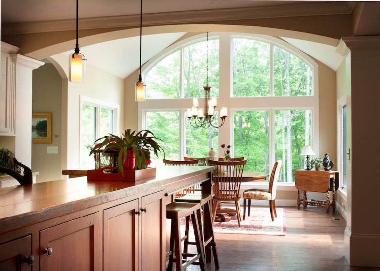 Kitchen island with view to floor to ceiling windows and tree outside